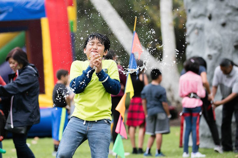child playing in rain at employee picnic