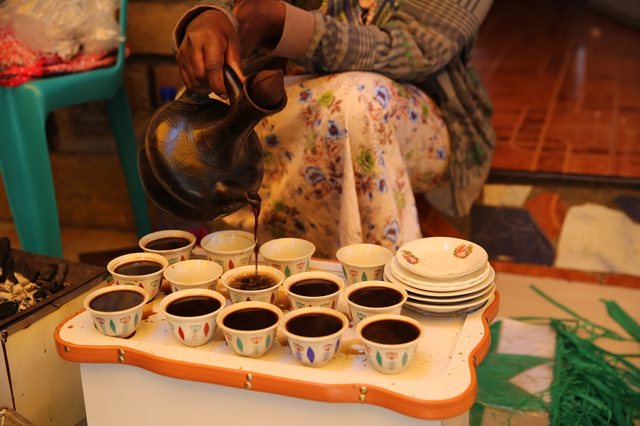 Woman pours coffee into small cups
