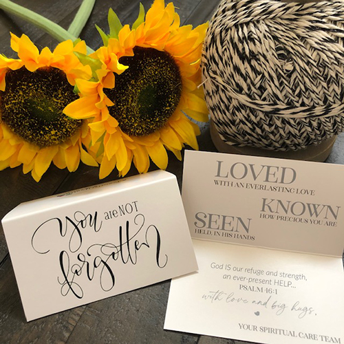 "Card that says ""You are not forgotten"" sitting on a table with sunflowers"