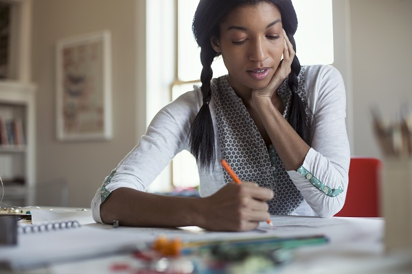 young woman making art at a table