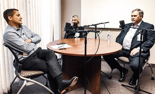 group of three people sitting at a circle table recording a podcast