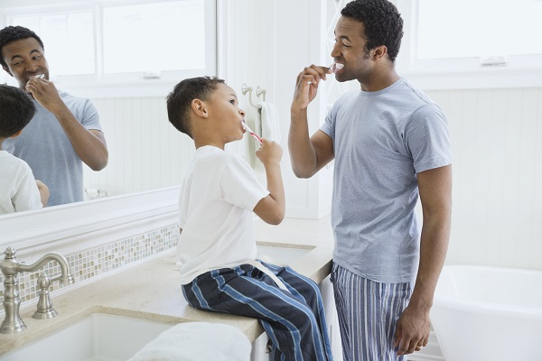 father and son brushing teeth in the morning