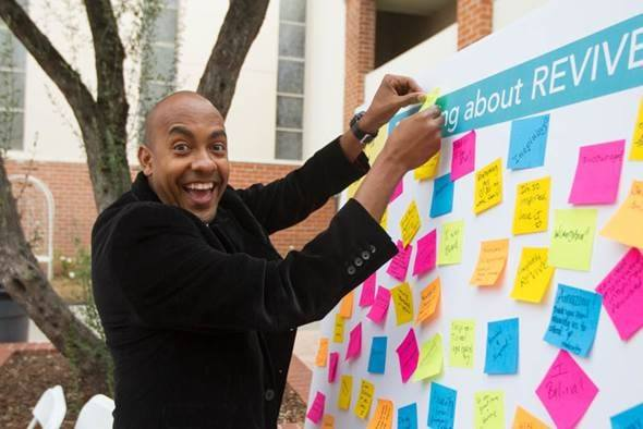 smiling man placing post-it on revival board