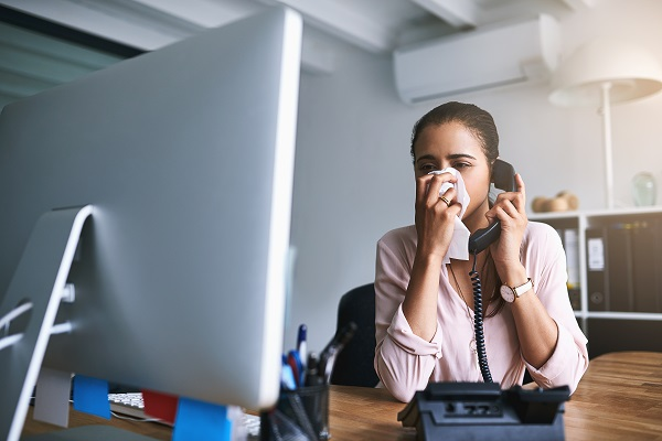 woman blowing her nose being sick at work