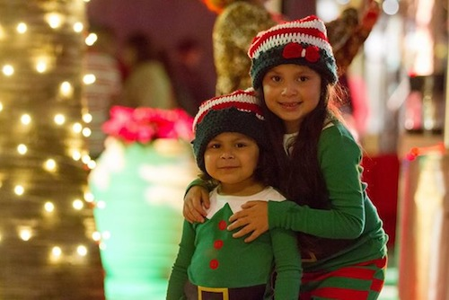 young girl and sibling dressed in elves outfits