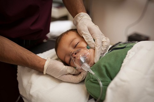 baby being treated with an oxygen mask