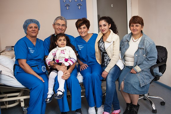 Mission Armenia caregivers in blue scrubs sitting in hospital room with a family