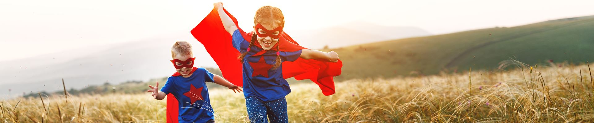 Two children in superhero capes play outside in a field or valley area.