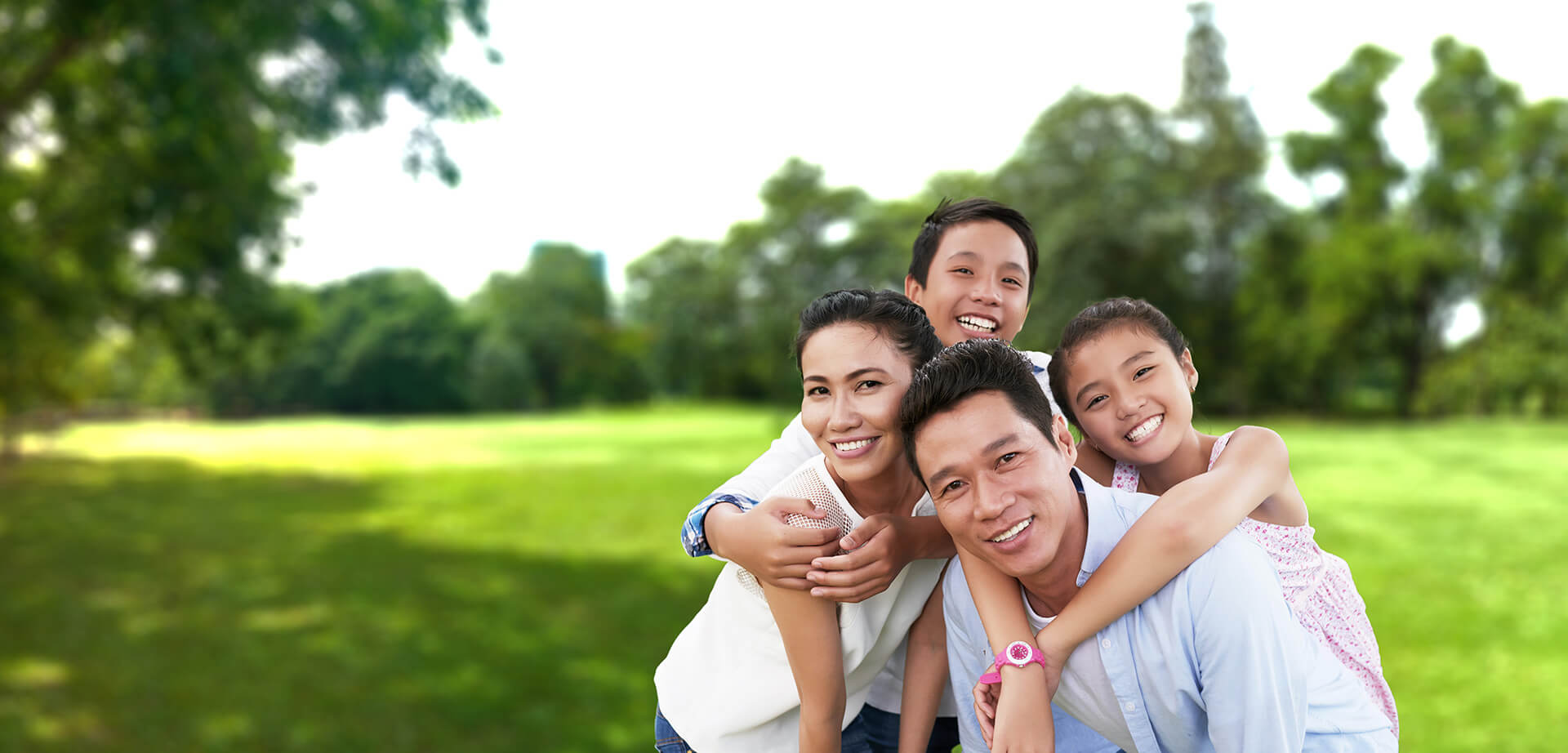 Asian couple with their two children hugging them in a green meadow