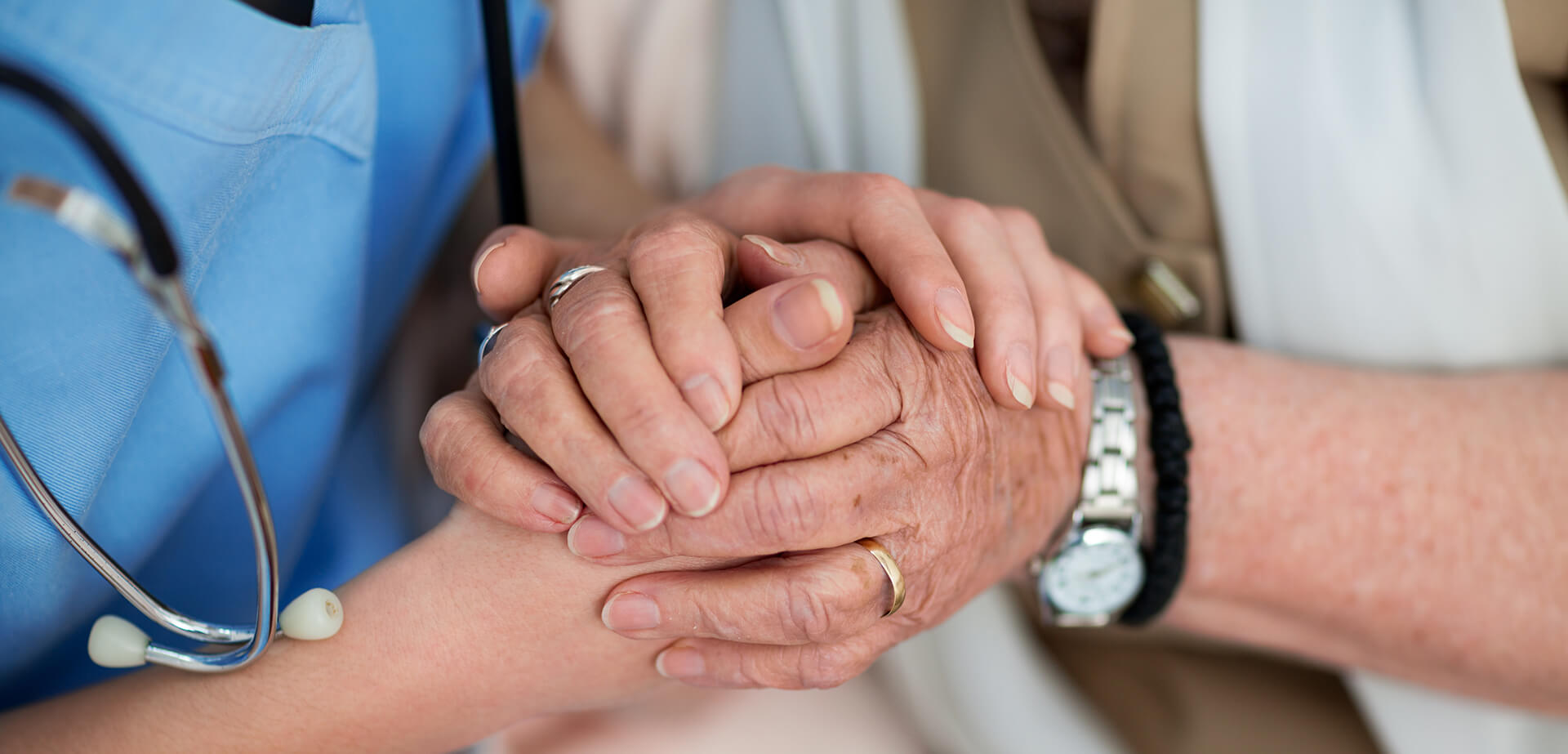 close-up of nurse holding the hands of an older woman