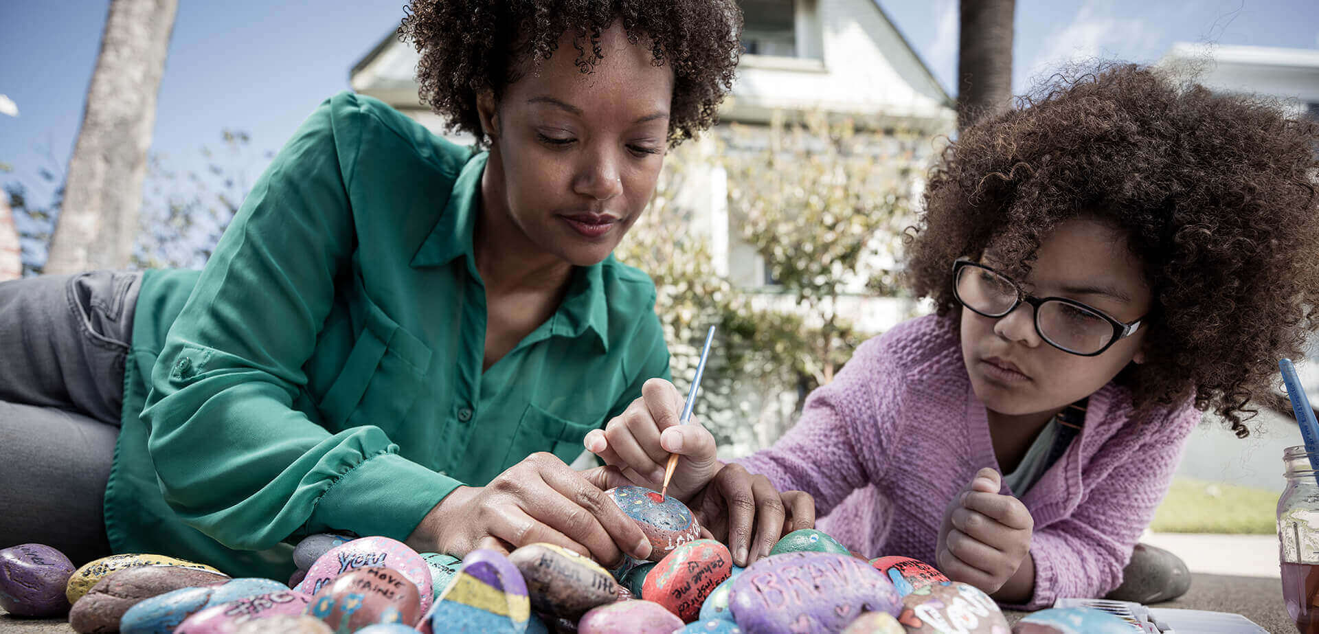 african american mother and young daughter in their yard painting rocks