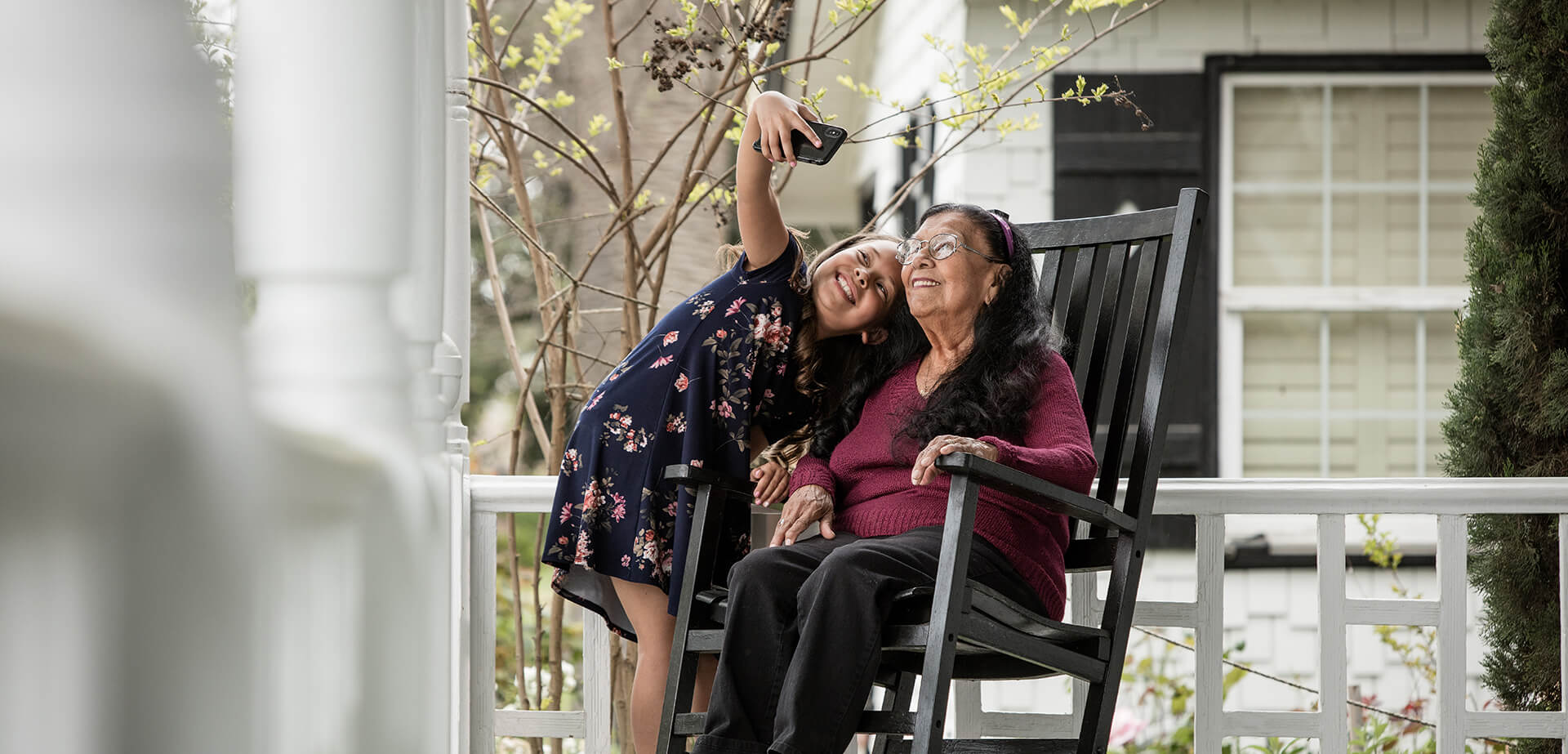 young girl and her grandmother on the front porch taking a selfie