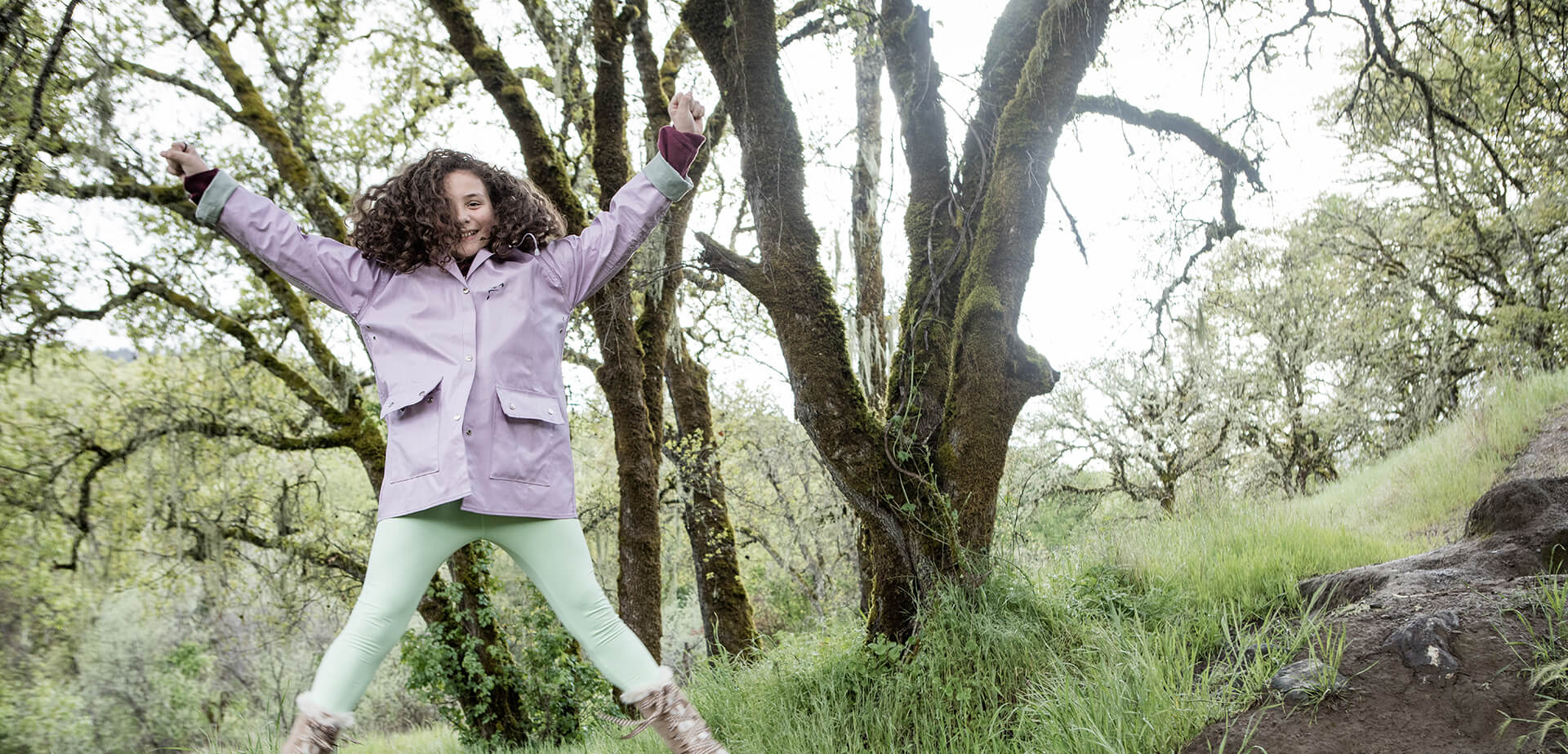 young curly haired brunette happily jumping in the air outdoors in a purple coat