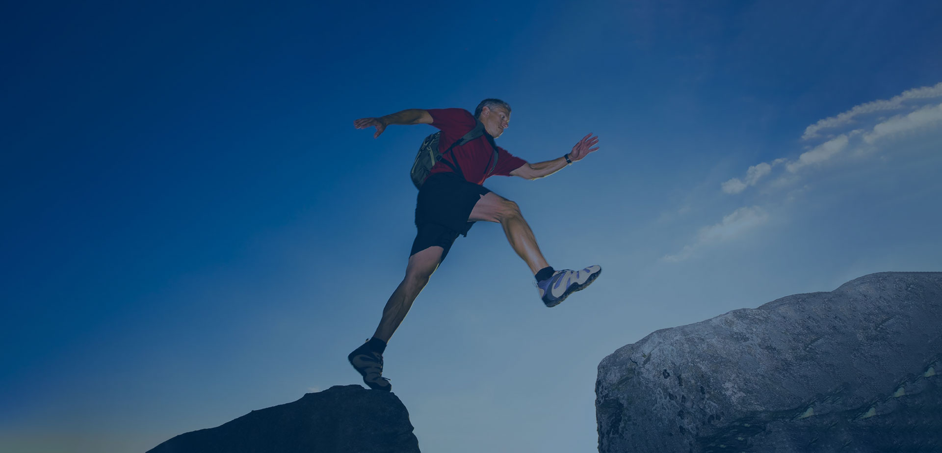 middle aged man wearing a backpack leaping from one boulder to another on a clear day