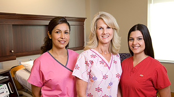 group of female nurses in pink and red scrubs