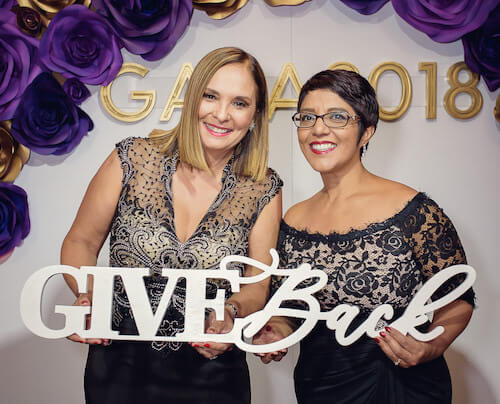 "two women in cocktail dresses at the Adventist Health White Memorial Gala 2018 holding the words ""give back"""
